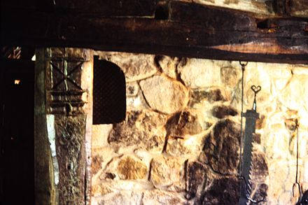 Traditional stone fireplace in northern England. The carved Saint Andrew's cross in the left hand wooden post was to prevent witches from flying down the chimney, Ryedale Folk Museum, Hutton-le-Hole. Cottage interior, Ryedale Folk Museum.jpg
