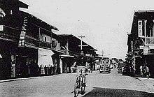 Man fietsen in de straat in de oude foto, met auto's op de achtergrond