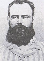Black and white photograph of the head and shoulders of a bearded man wearing a striped top