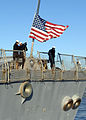 Defense.gov News Photo 101215-N-5292M-108 - Sailors aboard the guided-missile destroyer USS Stout DDG 55 remove the national ensign as the ship pulls away from the pier at Naval Station.jpg