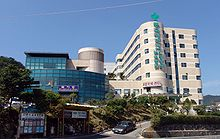 "A large seven-story hospital complex on a slope that consists of about two buildings. The wall of one on the left is covered with blue glasses, and the other building with round corners is covered with beige bricks. Large green vertical signs are attached on the wall of the latter. The signs say ""동국대학교 부속병원 한방병원"". In front of the hospital, a black car coming down from the slope."
