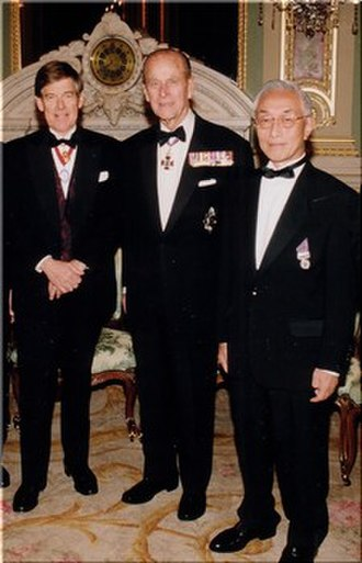 Medals of Honor (Japan) - Hitoshi Narita stands at near right, wearing the Japanese Medal of Honor with purple ribbon. Dr. Narita stands with H.R.H. Prince Philip, Duke of Edinburgh (middle) and with the President of the Royal Academy of Engineering, Alec Broers, now Lord Broers (left). The three men were photographed on the evening of a formal dinner following Narita's election as a fellow of the Academy in 2002.