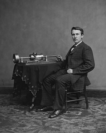 Photograph of Edison with his phonograph (2nd model), taken in Mathew Brady's Washington, D.C. studio in April 1878. Edison and phonograph edit1.jpg