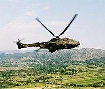 Een Cougar met beschildering SFOR vliegt over het landschap.jpg