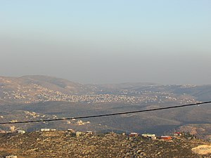 Einabus - In the front, beneath the telephone cable, is mount 725, an illegal Israeli outpost  of Yitzhar. Beneath it, crossed by the telephone cable, is Einabus. Covering most of the farther area is the municipality of Qabalan. Behing the right side of Qabalan is Talfit, and behind it is Qaryut. Behind the middle of Qabalan is Ahijah.