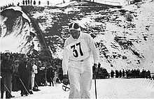 A man in white is pictured with a ski pole in his left hand. On his shirt is pinned a number tag with the number 37. Behind him to his right is a crowd of spectators at the side of a cross-country skiing course.