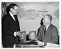 Emmet J. Kelley of the Assessing Department presents Mayor John F. Collins a plaque of the family crests of the Collins and Cundiff of Roscommon and Cork and Seal of the City of Boston (13852734645).jpg