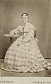 En kvinna poserar i en rutig långklänning - Nordiska Museet - NMA.0039776.jpg