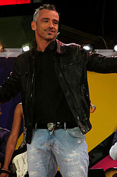 A man wearing a black leather jacket and blue jeans is performing