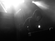 Justin Broadrick in a hoodie holding a guitar next to a Marshall amplifier