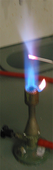 A flame with a small metal rod penetrating it; the flame near the rod is pale blue