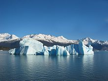 Photograph of an iceberg.  In the foreground a surface of water, in the center a light blue iceberg.  In the background snow-capped mountain peaks and a cloudless sky.