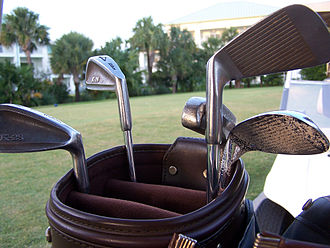 Golf club - Various golf clubs in a bag, including multiple irons, and a putter.