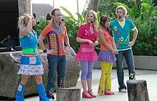 Foto de cuerpo entero de cinco artistas con ropas coloridas, de pie en un escenario al aire libre, la mayoría mirándose entre sí o entre la multitud.  La mujer de la izquierda tiene la mano derecha en el aire, los hombres tienen las manos en las caderas.  Llevan micrófonos de diadema y una gran pantalla de registro.