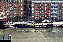 Photo de l'avion après sa récupération du fleuve, au premier plan. Ce dernier est installé au bord du quai et plusieurs navires sont présents sur la rivière.