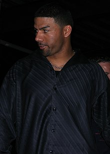 An olive-skinned man with a goatee wearing a black shirt