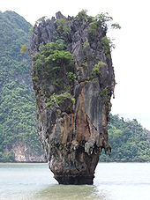 A tall rocky outcrop sitting in the sea, another island is visible, dominating the background.