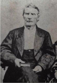 Un uomo anziano è seduto con un libro nella mano destra in grembo