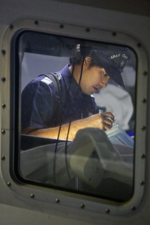 Japan Coast Guard - JCG officer conducts night inspection of a fishing boat