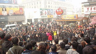 2011 Chinese pro-democracy protests - A large crowd of protesters, journalists, police and spectators gathered in front of a McDonald's restaurant in Wangfujing, Beijing.