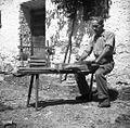 """Jože Florjančič z obličem prirezuje knjigo v preši; zraven je """"stou"""" za knjige šivat. Gorenji Novaki 1954.jpg"""