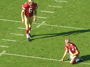 Holder (gridiron football) - San Francisco 49ers kicker Joe Nedney prepares to kick an extra point with punter Andy Lee as the holder, 2008
