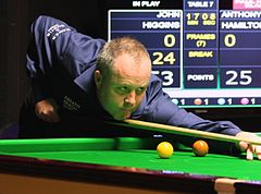Photograph of John Higgins wi a cue in haund, ready tae strike the cue ball.
