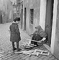 Jongetje kijkt hoe een oude vrouw een vuurtje maakt, Bestanddeelnr 254-5483.jpg