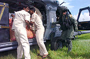Sri Lankan relief workers unload vegetables from an HH-60G Pave Hawk helicopter during an Operation Unified Assistance mission.