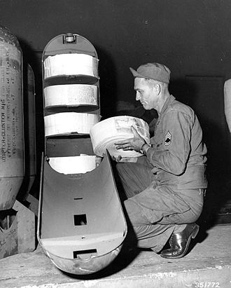 Airborne leaflet propaganda - An American leaflet bomb is loaded during the Korean War; the container holds 22,500 leaflets
