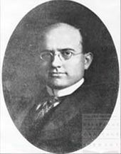 A black-and-white oval portrait of a bald man with spectacles in formal attire.