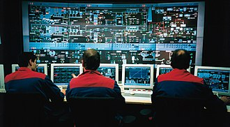 Industrial control system - A DCS control room where plant information and controls are displayed on computer graphics screens. The operators are seated as they can view and control any part of the process from their screens, whilst retaining a plant overview.