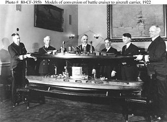 Lexington-class aircraft carrier - Rear Admiral David W. Taylor (left), Chief of the Bureau of Construction and Repair, and Rear Admiral John K. Robison (right), Chief of the Bureau of Engineering, hold a model of the battlecruiser above a model of the proposed conversion to an aircraft carrier at the Navy Department on 8 March 1922.