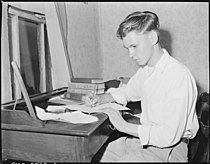 Louis Sergent, 16, who is in his first year at high school, does his homework. Both he and his father are determined... - NARA - 541288.jpg