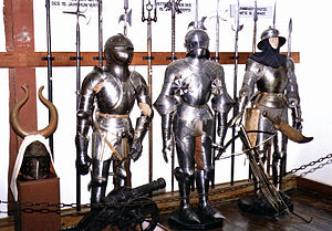 Gousset - Late fifteenth century gothic armor: the suit at left has gousset at the hip and probably included it at the elbow and armpit.  Gousset is visible at all of these locations on the suit at far right.