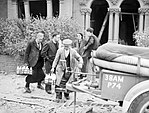 Milkmen deliver the morning round along a rubble strewn street, as householders discuss the damage to their properties following a V1 Flying Bomb attack in Upper Norwood, London, July 1944. D21231.jpg