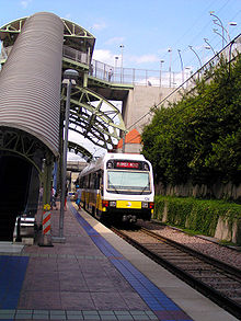 An escalator descends from the street to an island platform station with a white and yellow train present along a landscaped track.