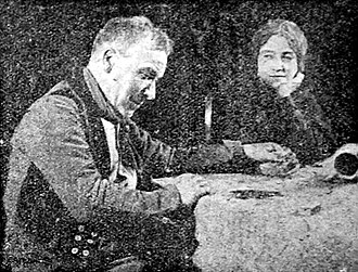 """My Old Dutch (1915 film) - Joe (Albert Chevalier) counts up his fast-dwindling savings with his """"Old Dutch"""" (Florence Turner)"""