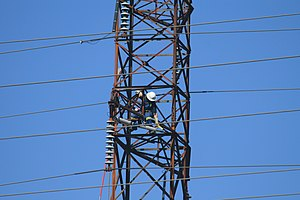 Lightning arrester - Powerline worker performs maintenance of a lightning arrester on an electrical transmission tower in New Brunswick, Canada.