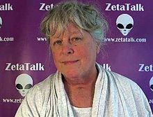 Nancy Lieder is seen from the neck up in front of a background of grey alien faces