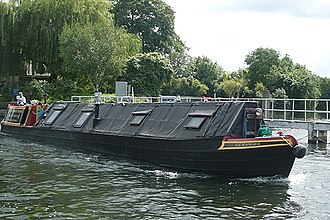 W.J. Yarwood & Sons - A converted working narrowboat, Clypeus, opens up leaving Penton Hook Lock heading upstream past the weir. Clypeus is number 28 in the Grand Union Canal Carrying Company fleet, being one of 12 iron composite pairs of Star Class boats built by Yarwoods of Northwich in 1935.