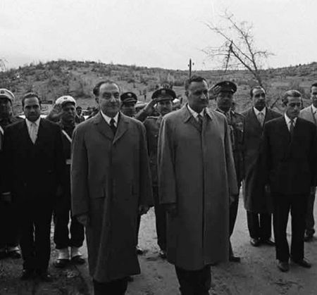 Two men standing side-by-side in the forefront, wearing overcoats. Behind them are several men in military uniform or suits and ties standing and saluting or making no gestures.