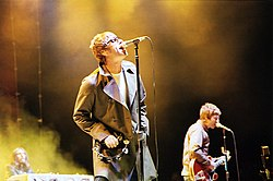 Oasis performing live. From left to right: Jay Darlington (background), Liam Gallagher, Noel Gallagher.