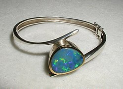 The opal in this bracelet contains a natural periodic microstructure responsible for its iridescent color. It is essentially a natural photonic crystal, although it does not have a complete photonic band gap.