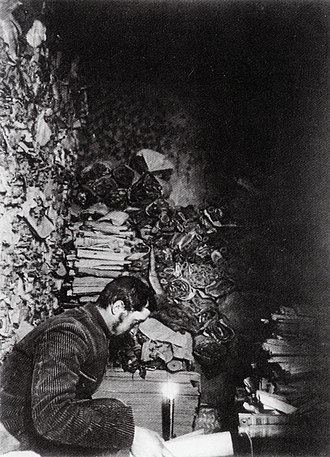 Paul Pelliot examines manuscripts in cave 17 Paul Pelliot examining manuscripts in Cave 17 at Mogao Caves in 1908.jpg