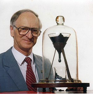 Pitch drop experiment - The University of Queensland pitch drop experiment, featuring its then-current custodian, Professor John Mainstone (taken in 1990, two years after the seventh drop and 10 years before the eighth drop fell).