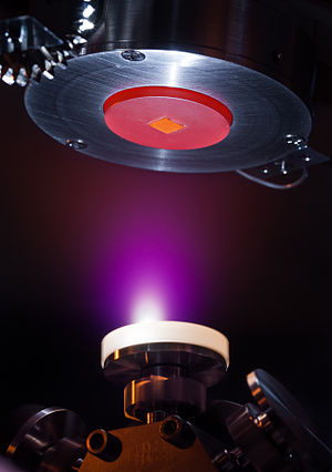 Pulsed laser deposition - Thin films of oxides are deposited with atomic layer precision using pulsed laser deposition. In this picture, a high-intensity pulsed laser shoots a rotating white disk of Al2O3 (alumina). The laser pulse creates a plasma explosion, visible as the purple cloud. The plasma cloud from the alumina expands towards the square substrate, made of SrTiO3, where it condenses and solidifies, building up one atomic layer at a time. The substrate is mounted on a heating plate, glowing red at a temperature of 650 °C, to improve the crystallinity of the alumina thin film.