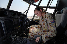A woman wearing a camouflaged military uniform sitting in the cockpit of an aircraft