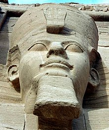 One of the four external seated statuesof Ramesses II at ابوسمبل.