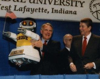 John Mutz - Mutz holding a robot built by Purdue Students in 1987